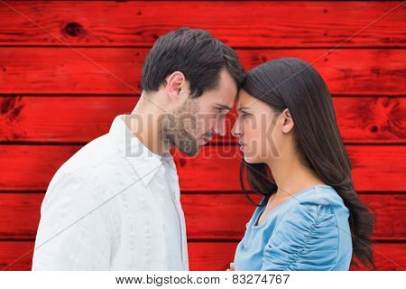 Angry couple staring at each other against red wooden planks