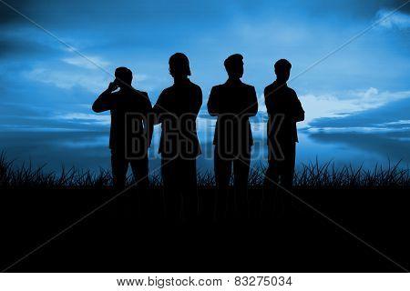 Silhouette of businessmen against blue sky over grass