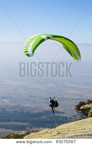 Paraglider takes off from a rocky mountain