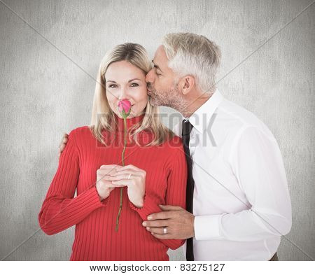 Handsome man giving his wife a kiss on cheek against weathered surface