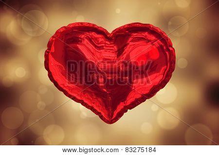 Red heart balloon against orange abstract light spot design