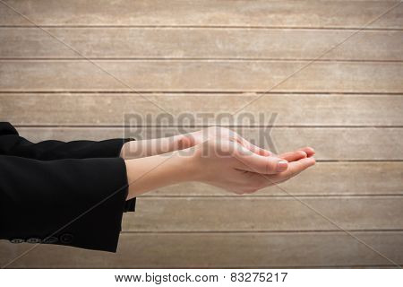 Businesswomans hands presenting against wooden surface with planks