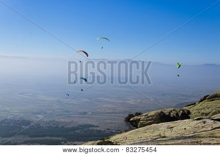 Paragliding against clear blue sky