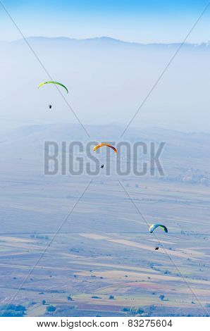 Paragliders flying against blue sky