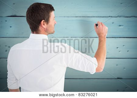 Business man writing with chalk against painted blue wooden planks