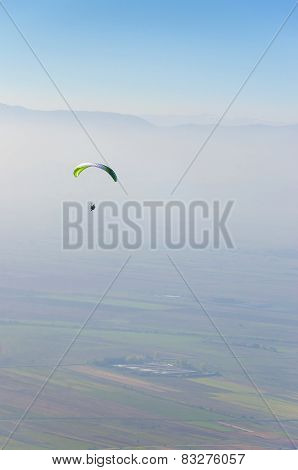 Paragliding high above the fields on blue sky