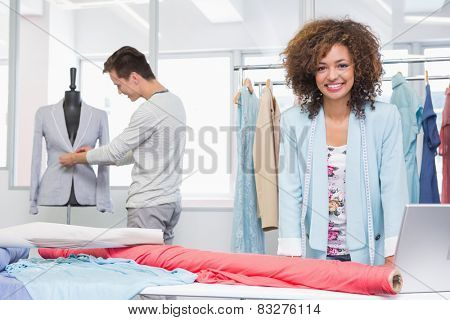 Smiling students working with fabric and model at the college
