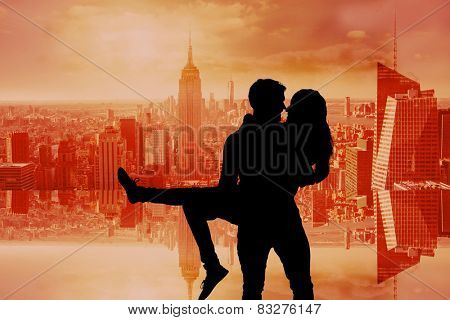 Attractive young couple having fun against room with large window looking on city