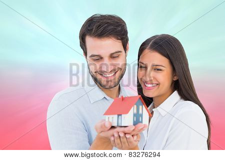 Attractive young couple holding a model house against blue and pink light spot design