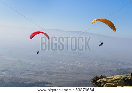 Two paragliders flying high above the mountain
