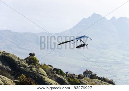 Hand glider taking off of a mountain