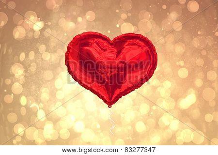 Red heart balloon against yellow abstract light spot design