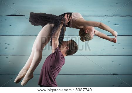 Ballet partners dancing against painted blue wooden planks