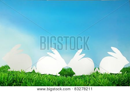 Paper Easter rabbits on green grass, on sky background