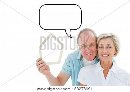 Happy older couple holding house shape against speech bubble