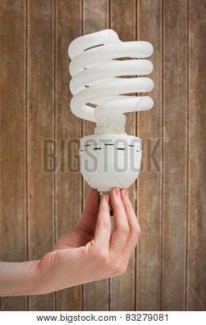 Hand holding energy efficient light bulb against wooden planks background