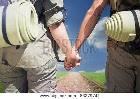 Hitch hiking couple standing holding hands on the road against path on grass