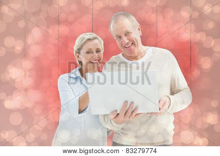 Happy mature couple using laptop against light glowing dots design pattern