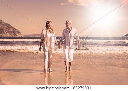 Happy couple walking barefoot on the beach on a sunny day