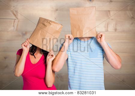 Young couple with bags over heads against bleached wooden planks background