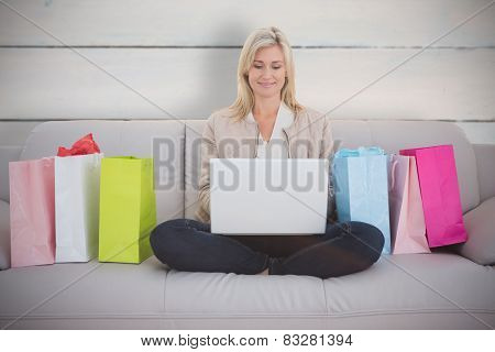 Woman shopping online against painted blue wooden planks