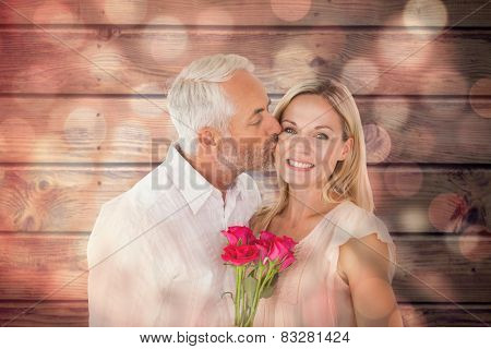 Affectionate man kissing his wife on the cheek with roses against light circles on black background