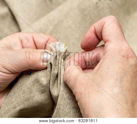 Closeup of senior woman's hands basting linen border with needle and thread