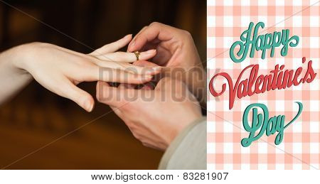 Close up on man putting on ring during marriage proposal against happy valentines day