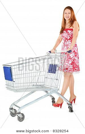 joyful woman wearing dress is standing with shopping basket. isolated.