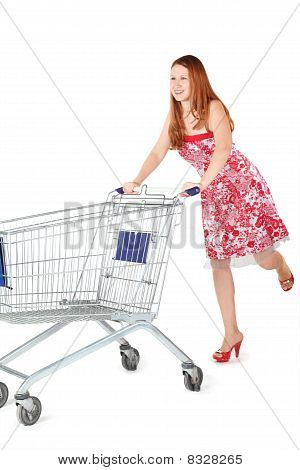 woman wearing dress is moving shopping basket. isolated.