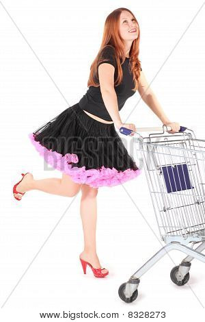 woman wearing dress is moving shoping basket and looking away. isolated