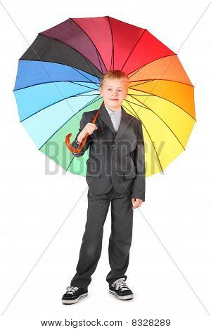 boy wearing suit and sneakers is standing with colored umbrella