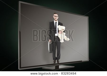 Geeky businessman holding briefcase and teddy against green background with vignette