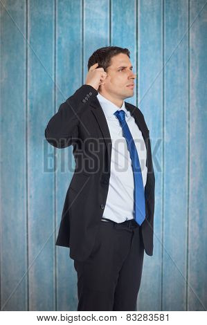 Thinking businessman scratching head against wooden planks