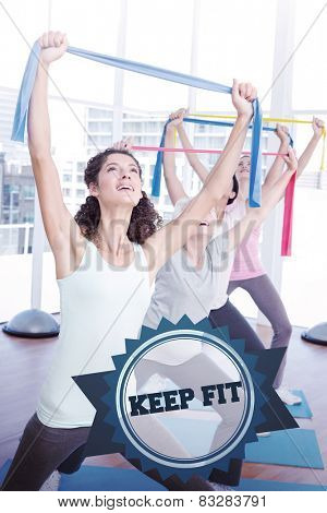 The word keep fit and class holding up exercise belts at yoga class against badge