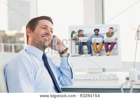 Male designers working together with laptops against smiling businessman phoning at his desk