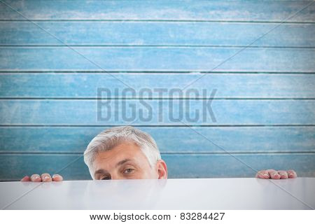 Businessman peeking over desk against wooden planks