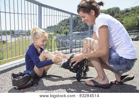 A Little girl with is mother in roller skates at a park