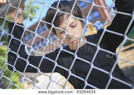 A sad boy on a school playground closing