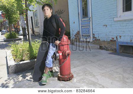 A Teenager boy portrait with skateboard on a urban scene.