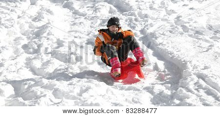 Child Plays With Sled In The Snow In Winter