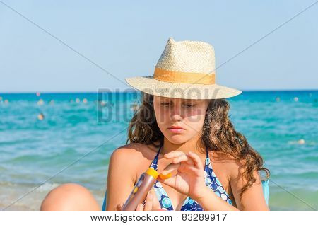 Gorgeous girl applying sun block cream on the beach