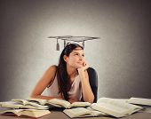 stock photo of graduation  - Young student between books dreams the graduation - JPG