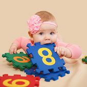 stock photo of nibbling  - Smart baby playing and nibbling figures and numbers on a beige background - JPG
