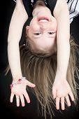 foto of upside  - Happy little girl hanging upside down isolated on black - JPG