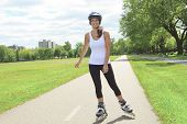 picture of inline skating  - A Roller skating girl in park rollerblading on inline skates - JPG