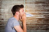 picture of blow-up  - Close up side view of man blowing nose against wooden planks - JPG