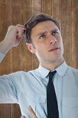image of scratching head  - Thinking businessman scratching head against wooden planks background - JPG