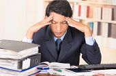 picture of overwhelming  - young stressed overwhelmed business man holding head with his hands looking at piles of folders on his desk - JPG