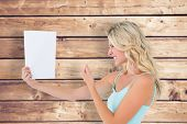 pic of outrageous  - Angry blonde looking at page against wooden planks background - JPG